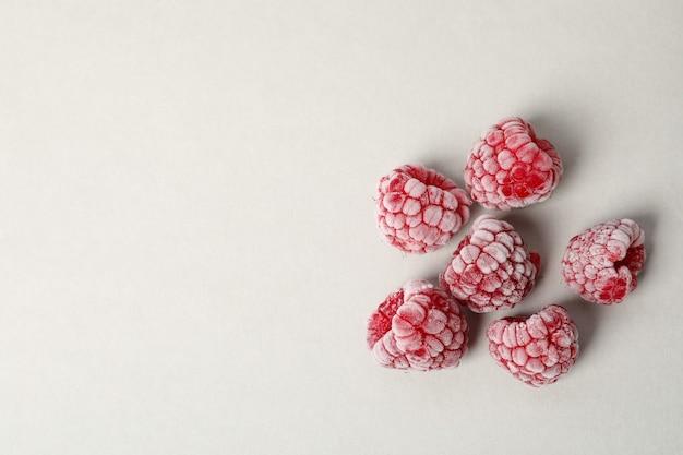 Group of frozen raspberry on light gray background