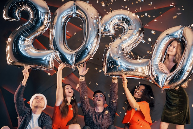 A group of fun young beautiful multinational people throwing confetti at a party. happy new year.