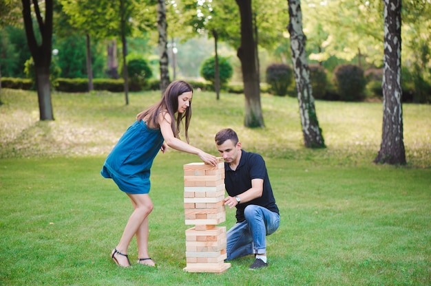 Групповая игра физического мастерства с большими блоками на зеленой траве.