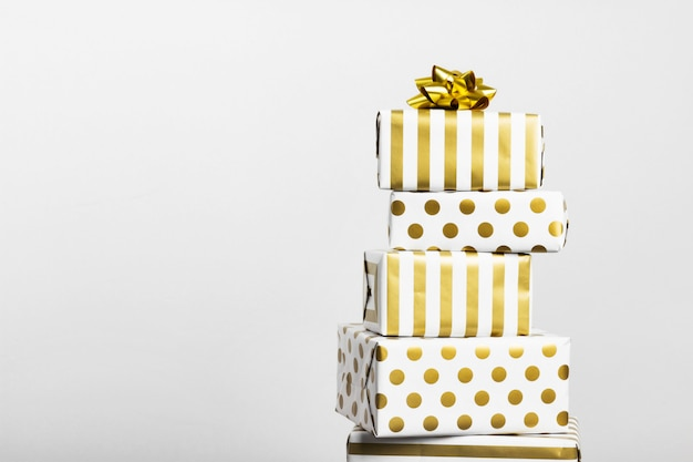 Group of gifts in white and gold paper on gray.