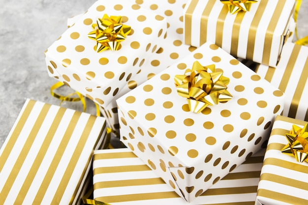 Group of gifts in white and gold paper on gray