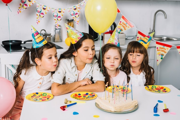 Group of girls blowing candles on birthday cake