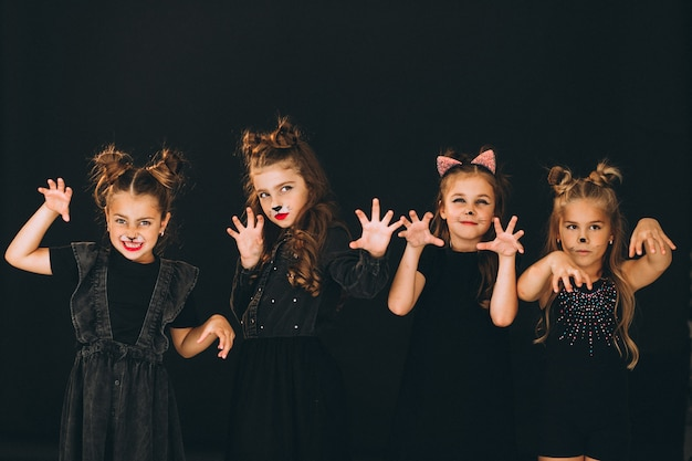Group of girls dressed in halloween costumes in studio