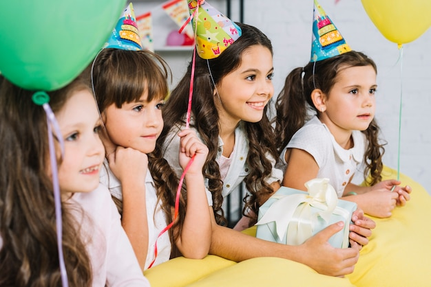 Group of girls wearing party hats and balloons looking away