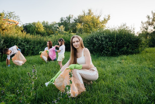 A group of girls with children at sunset are engaged in garbage collection in the park. environmental care, recycling.
