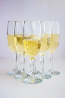 A group of glasses with champagne on a white background.