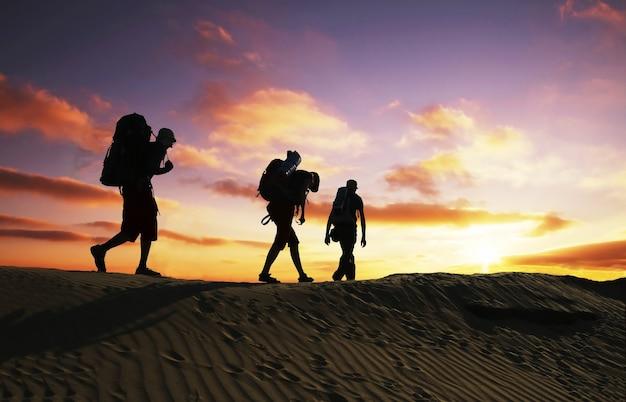 Группа идет по холму на закате