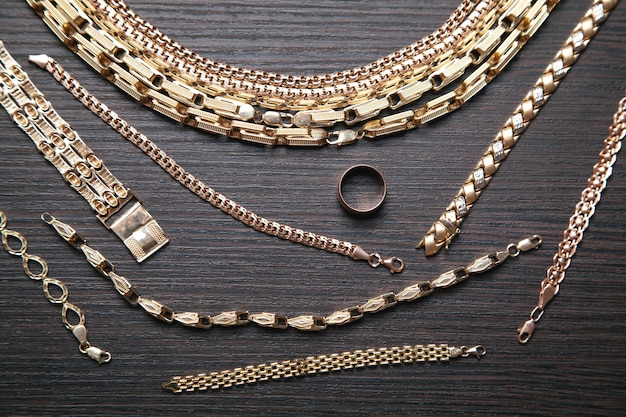 Group of gold jewelry on dark background.