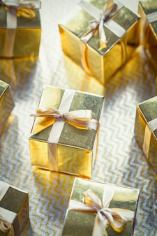 Group of gold sparkling gift boxes, beautiful gold packaging surprise with bow on sparkling background