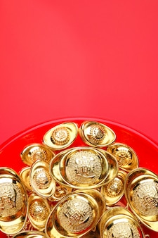 Group of golden ingots on red tray at red background.chinese language on ingot mean wealth