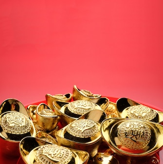 Group of golden ingots on red tray at red background.chinese new year