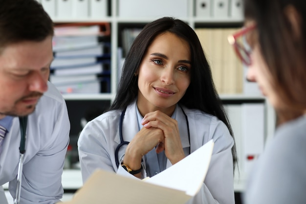 Group of gp consulting young woman in office