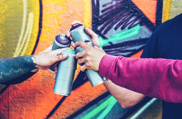 Group of graffiti artists stacking hands while holding spray color cans