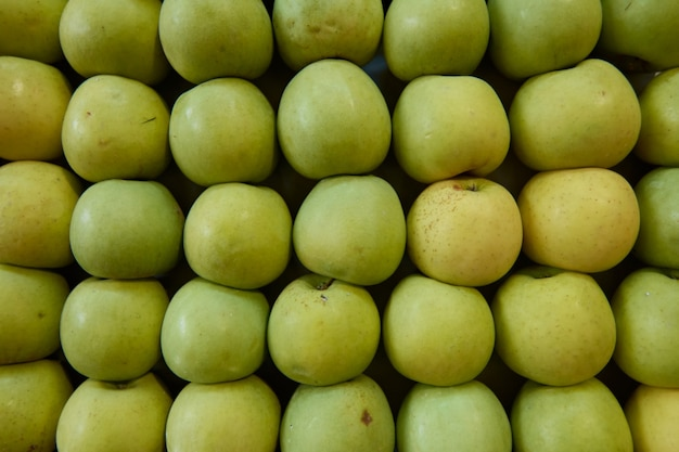 A group of green apples stacked toghether in order