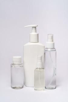 Group of hand sanitizer spray or liquid soap bottles over light grey table