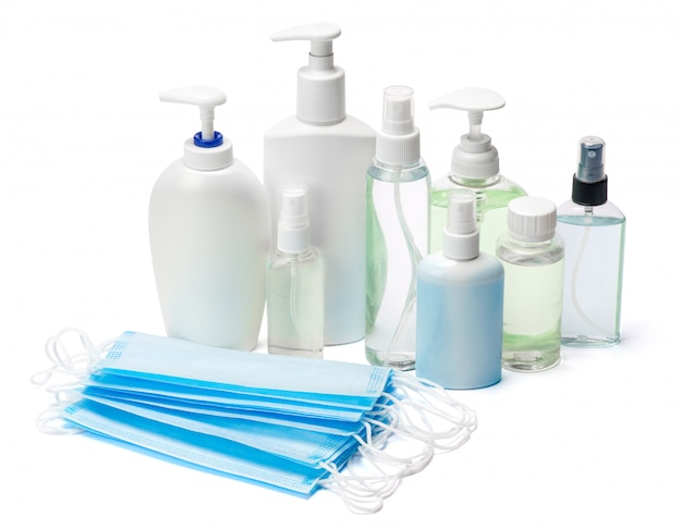 Group of hand sanitizer spray and liquid soap bottles and protective masks on white table