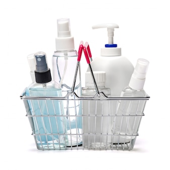 Group of hand sanitizer spray and liquid soap bottles in small shopping basket on white table