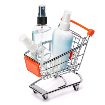 Group of hand sanitizer spray and liquid soap bottles in small shopping cart basket on white table