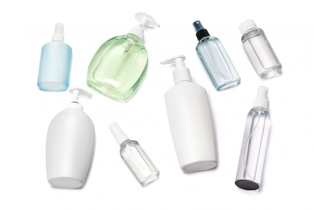 Group of hand sanitizer spray and liquid soap bottles on white table