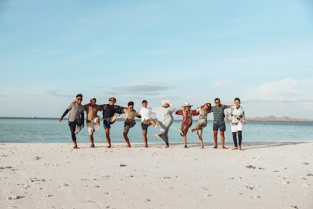 Group of happy asian friends enjoying vacation with embrace each other and dance on the beach