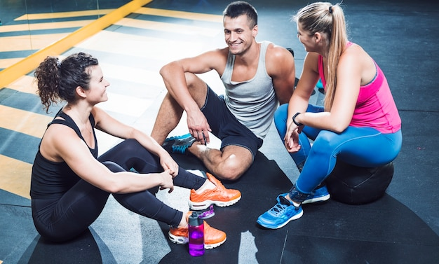 Group of happy athletic people sitting on floor after workout in health club