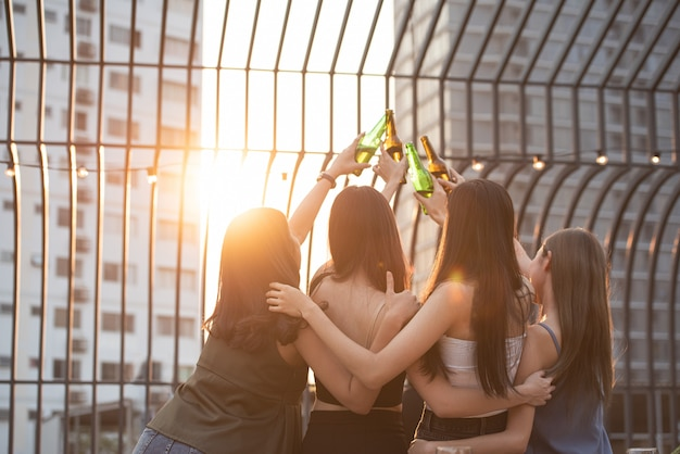 Group of happy beautiful young asian woman friends on back or rear side raised hand hold bottle of beer dance and toast together on outdoor rooftop terrace in evening of outdoors club.