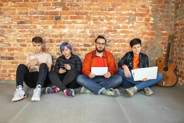 Gruppo di giovani caucasici felici che si siedono dietro il muro di mattoni.