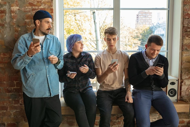 Group of happy caucasian young people standing behind the window. sharing a news, photos or videos from smartphones, talking or playing games and having fun. social media, modern technologies.
