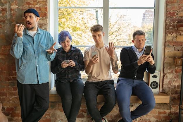 Gruppo di giovani caucasici felici in piedi dietro la finestra. condividere notizie, foto o video da smartphone, parlare o giocare e divertirsi. social media, moderne tecnologie.