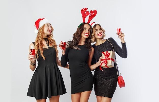 Gruppo di donne felici di celebrazione in cappelli di travestimento del partito di capodanno carino trascorrere del tempo insieme bere alcol, ballare, divertirsi su sfondo bianco.