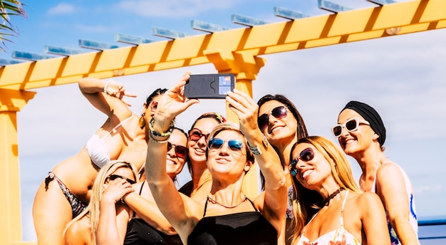 Group of happy and cheerful young caucasian women have fun together in friendship taking selfie picture during summer holiday vacation