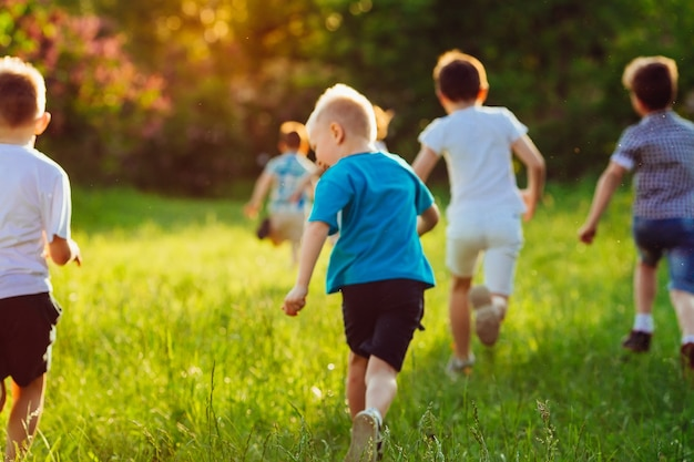 A group of happy children of boys and girls run in the park on the grass on a sunny summer day.