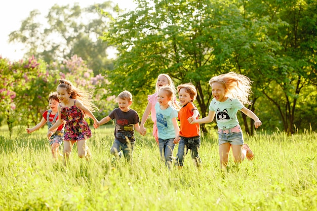 A group of happy children of boys and girls run in the park on the grass on a sunny summer day