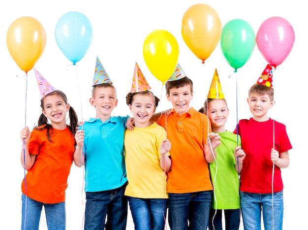Gruppo di bambini felici in magliette colorate con palloncini su sfondo bianco