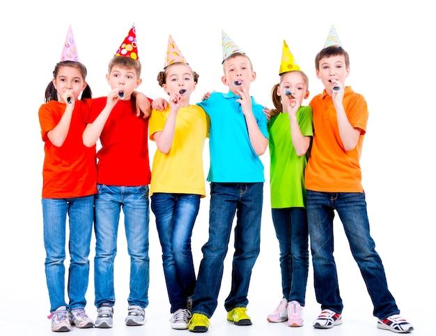 Gruppo di bambini felici in magliette colorate con ventilatori di partito - isolato su uno sfondo bianco