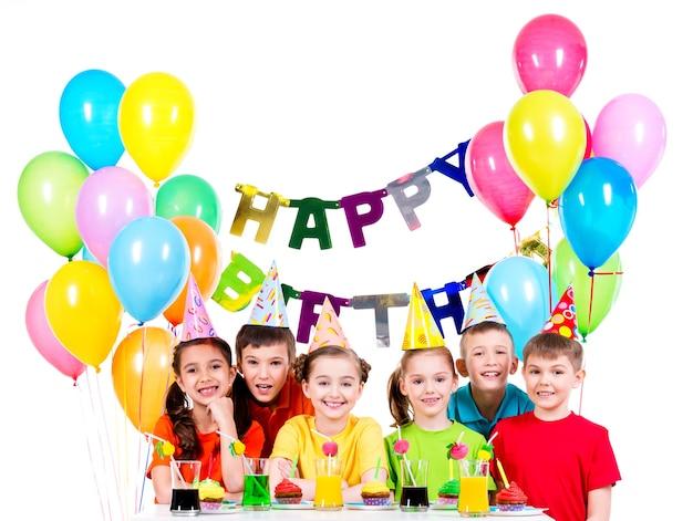 Gruppo di bambini felici in camicie colorate divertendosi alla festa di compleanno - isolato su un bianco