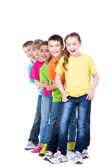Group of happy children in colorful t-shirts stand behind each other on white wall.