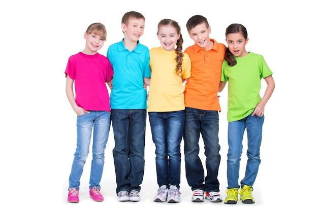 Gruppo di bambini felici in magliette colorate che stanno insieme in piena lunghezza su sfondo bianco.