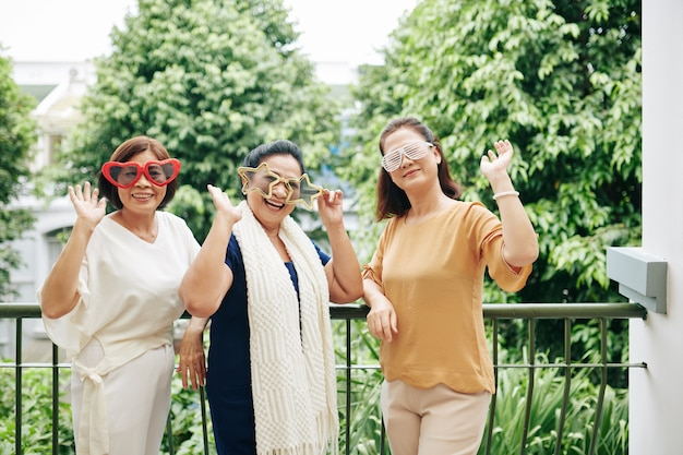 Group of happy excited senior women in funny glasses having fun at home party