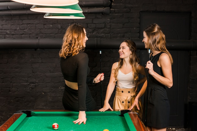 Group of happy female friends standing near snooker table