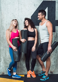 Group of happy fit people leaning on wall in gym