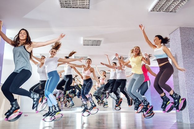 Group of happy fit young women jumping in kangoo jumps footwear in fitness studio.