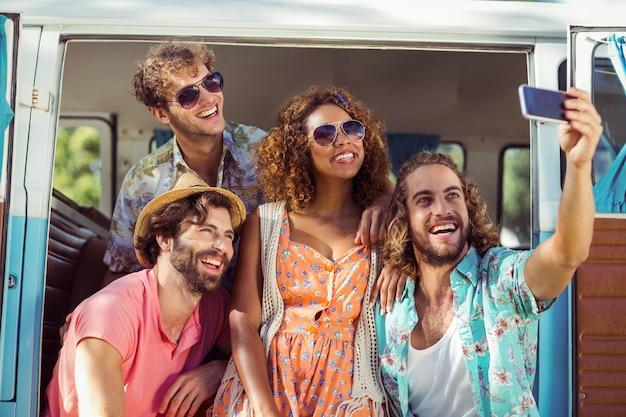 Group of happy friend taking a selfie in campervan