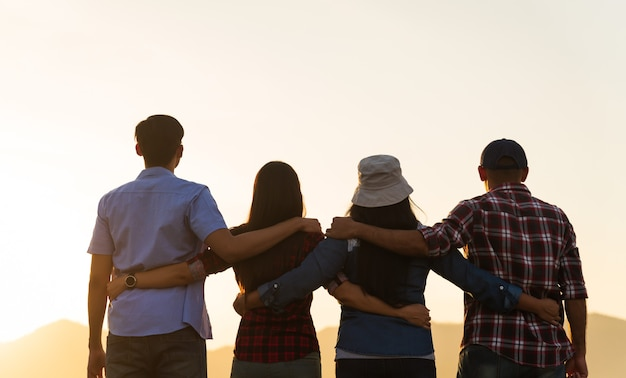 Group of happy friends are having fun with holding together in front of mountain