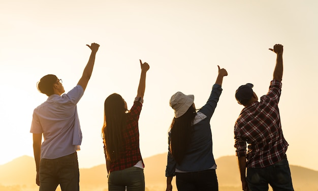 Group of happy friends are having fun with raised arms together