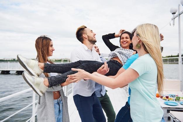 Gruppo di amici felici in spiaggia, uomo che lancia una donna felice.