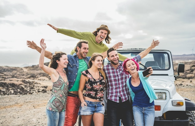 Group of happy friends doing excursion on desert in convertible 4x4 car - young people having fun traveling together - friendship, tour, youth, lifestyle and vacation concept - focus on guys faces