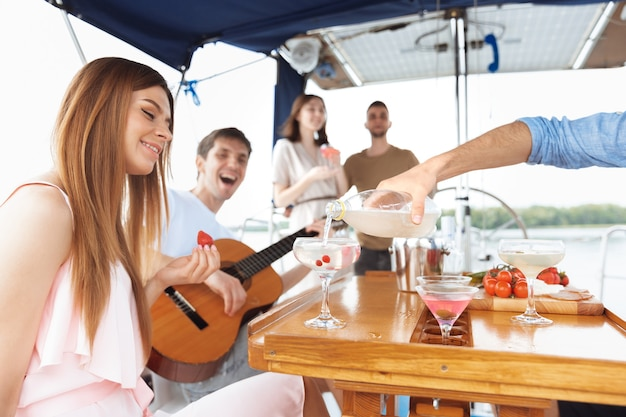 Group of happy friends drinking vodka cocktails at boat party outdoor, summer