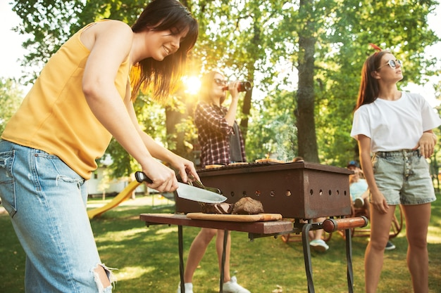 Group of happy friends having beer and barbecue party at sunny day. resting together outdoor in a forest glade or backyard