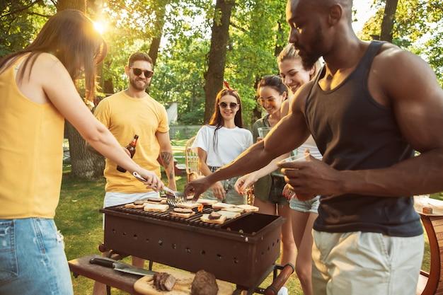 Gruppo di amici felici che hanno birra e barbecue party in giornata di sole. riposare insieme all'aperto in una radura della foresta o in un cortile